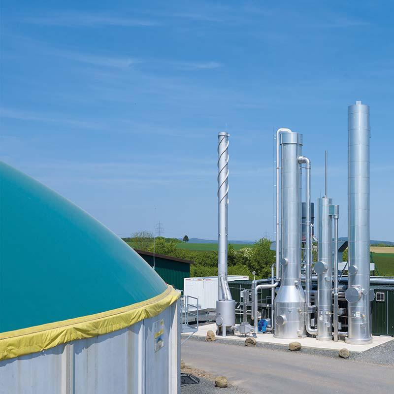 Produkte und Dienstleistungen für Biogas Anlagenbetreiber. Hier zu sehen eine Biomethananlage. Im Vordergrund der Fermenter und im Hintergrund die Gasaufbereitung